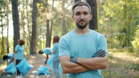 Portrait of eco-friendly man volunteer standing in forest with arms crossed Live Action