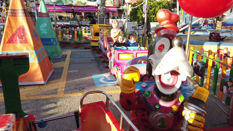 Young Children Ride On A Colorful Train Carousel Live Action