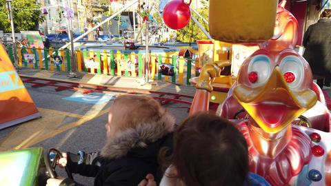 Children Ride On A Colorful Train Carousel Live Action