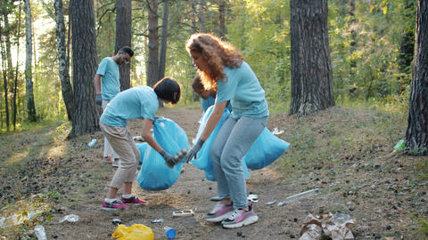 Youth volunteers collecting trash bottles and plastic from ground in polluted Live Action