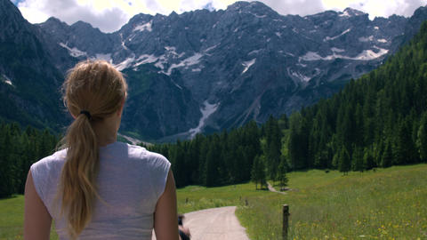 Mid shot - Behind young woman walking to the mountains with hiking poles Footage