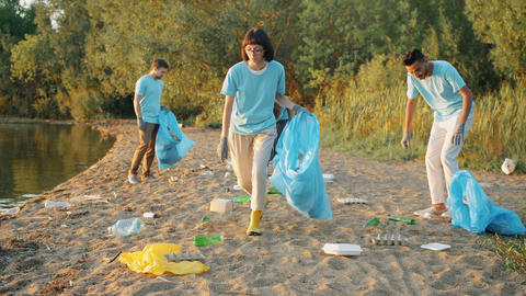Multi-ethnic group of students cleaning beach from pollution during Earth day Live Action