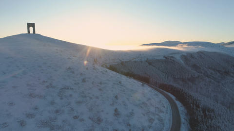 Aerial view of susnet over snowy misty mountains with slippery mountain winding Live Action