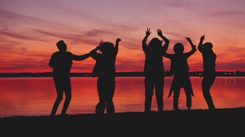 Excited youth dancing near lake on sun-down then doing high-five and hugging Live Action