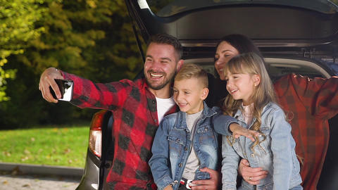 Attractive portrait of modern beautiful smiling family which sitting in the car Live Action