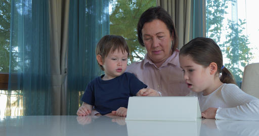 Grandma entertaining her little grandchildren with a tablet computer game Live Action