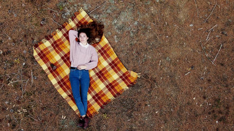 AERIAL: A beautiful young woman lies on a carpet in the middle of the pine Live Action
