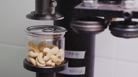 employee closes jar of cashew nuts with cap at workplace Live Action