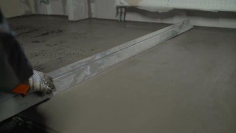 Leveling the floor with a spatula. Builder smoothing wet mortar on the floor Live Action