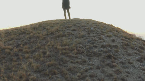 A man in a suit stands on top of a hill and looks at the dawn over the sea Live Action