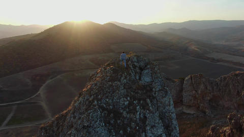 AERIAL: Men climbed to the top of the mountain to enjoy the sunset Man stands Live Action