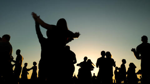 People silhouettes learning how to dance on city quay at sunset - slow motion Live Action