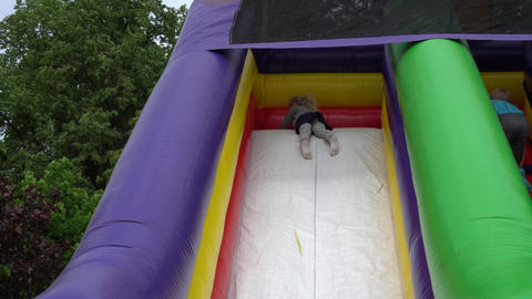playful girl slide down on inflatable playground trampoline. Gimbal follow shot Live Action