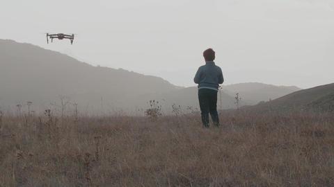 Boy controls drone amid hills GIF