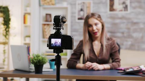 Zoom in shot of female makeup artist recording a vlog Live Action