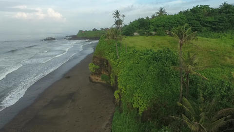 Drone footage of the shoreline of Bali with a small cliff and lots of grass Live Action