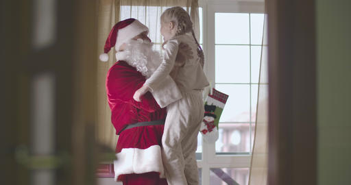 Portrait of cheerful Caucasian man in Santa Claus costume holding cute Caucasian Live Action