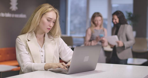 Portrait of young serious Caucasian woman typing on laptop keyboard. Portrait of Live Action