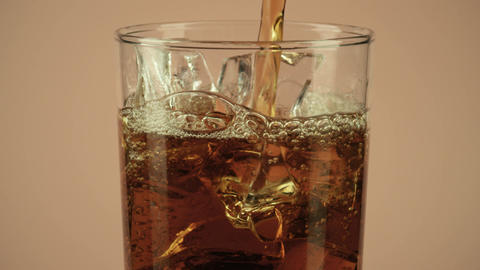 Pouring brown drink into a glass with ice against brown background, close-up Live Action