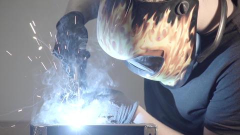 man is welding with a welding helmet Live Action