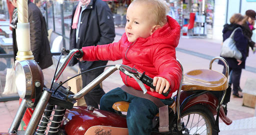 Baby Boy Sitting On A Vintage Motorcycle In A Carousel Merry-Go-Round GIF