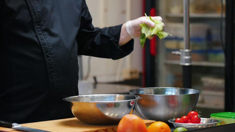 Kitchen - chef making a salad - putting a salad leaves in the deep plate Live Action