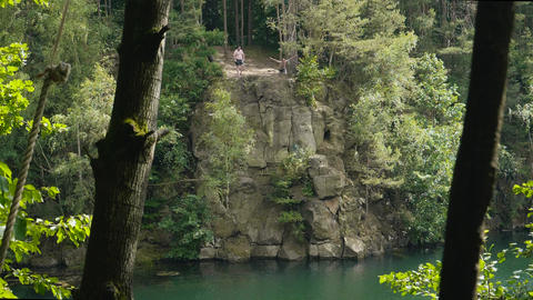 Young Adult jumping off a high cliff in beautiful lake in sunny summer in 4k slow motion Live Action
