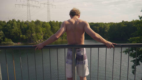 Young Adult jumps off a high bridge into beautiful lake in sunny summer in 4k super slow motion Live Action