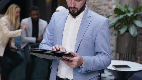 Portrait shot of professional caucasian businessman making notes in tablet Live Action