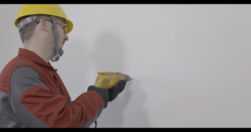 Worker using a drilling machine and drilling hole in the wall Live Action