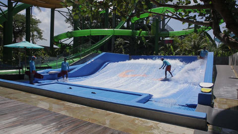 People are surfing on a surf machine at the resort on Bali, Indonesia Live Action