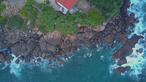 camera rises above temple on steepy cliff near calm ocean Live Action