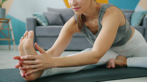 Low shot of flexible young woman doing yoga at home bending to foot on mat Live Action
