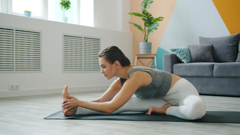 Carefree girl bending to one leg developing flexibility doing yoga alone at home Live Action