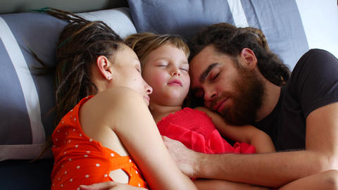 Family with a child sleeping on the bed. Daytime sleep with the whole family Live Action