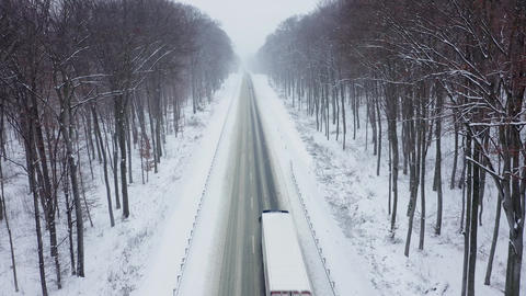 Aerial view of truck driving on a road surrounded by winter forest in snowfall Live Action