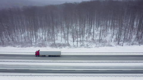 Aerial view of traffic on a road surrounded by winter forest in snowfall Live Action
