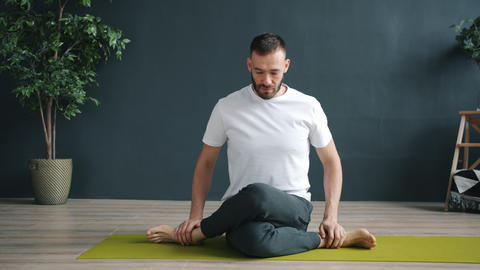 Male adult doing yoga alone exercising in cow face position in wellness center Live Action