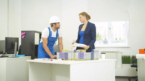 Builder and woman discuss models of houses, they rearrange houses on table Live Action