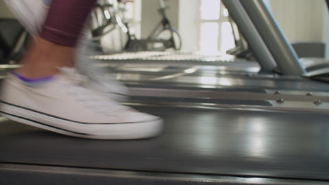 Slim female legs running on treadmill at gym Live Action