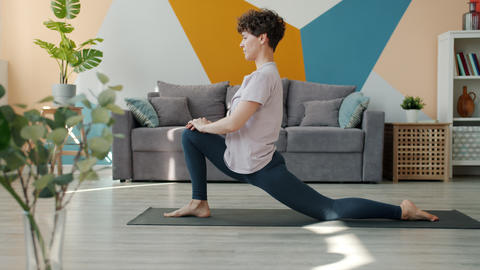 Flexible young woman doing yoga in house practising asanas alone on comfy mat Live Action