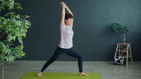 Active young woman doing yoga in studio exercising alone…, Live Action