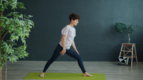 Active young woman doing yoga in studio exercising alone indoors in cozy room Live Action