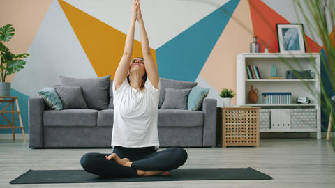Attractive young woman in modern clothing exercising at home in lotus position Live Action