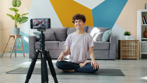 Smiling yoga instructor recording tutorial at home vlogging using smartphone Live Action