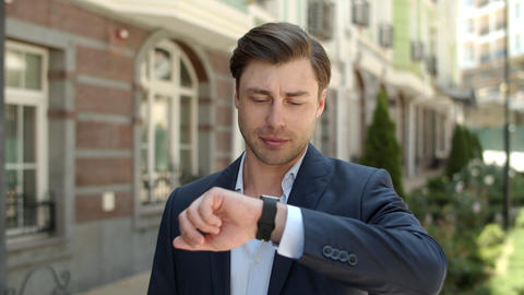 Portrait man using smart watch outdoors. Man looking on smart watch at street Live Action
