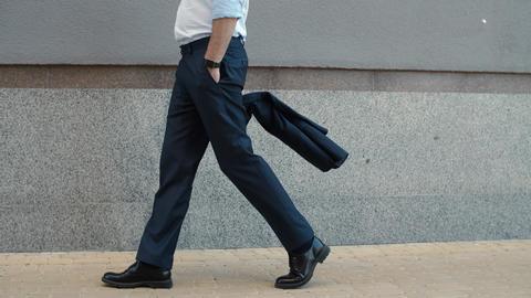 Closeup businessman walking near building. Businessman stretching neck outdoor Live Action