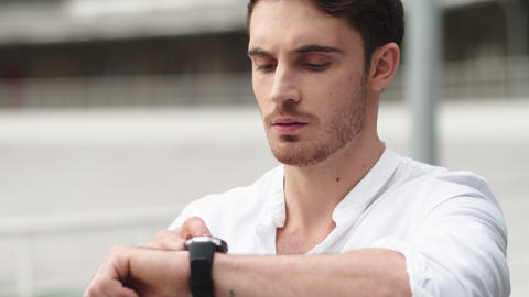 Closeup guy checking time on smart watch . Portrait man using digital watch Live Action