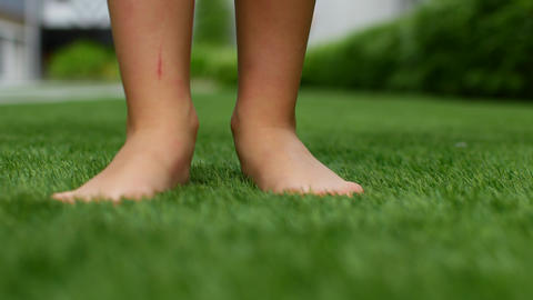 Bare feet on the grass. The green grass in the park beckons to be barefoot Live Action