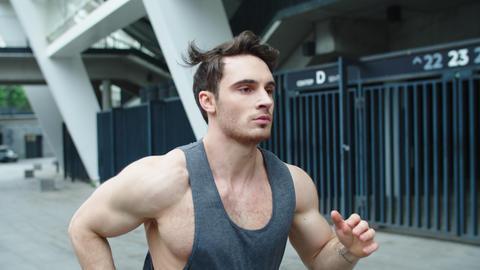 Handsome man running on urban street. Portrait muscular man jogging outdoor Live Action